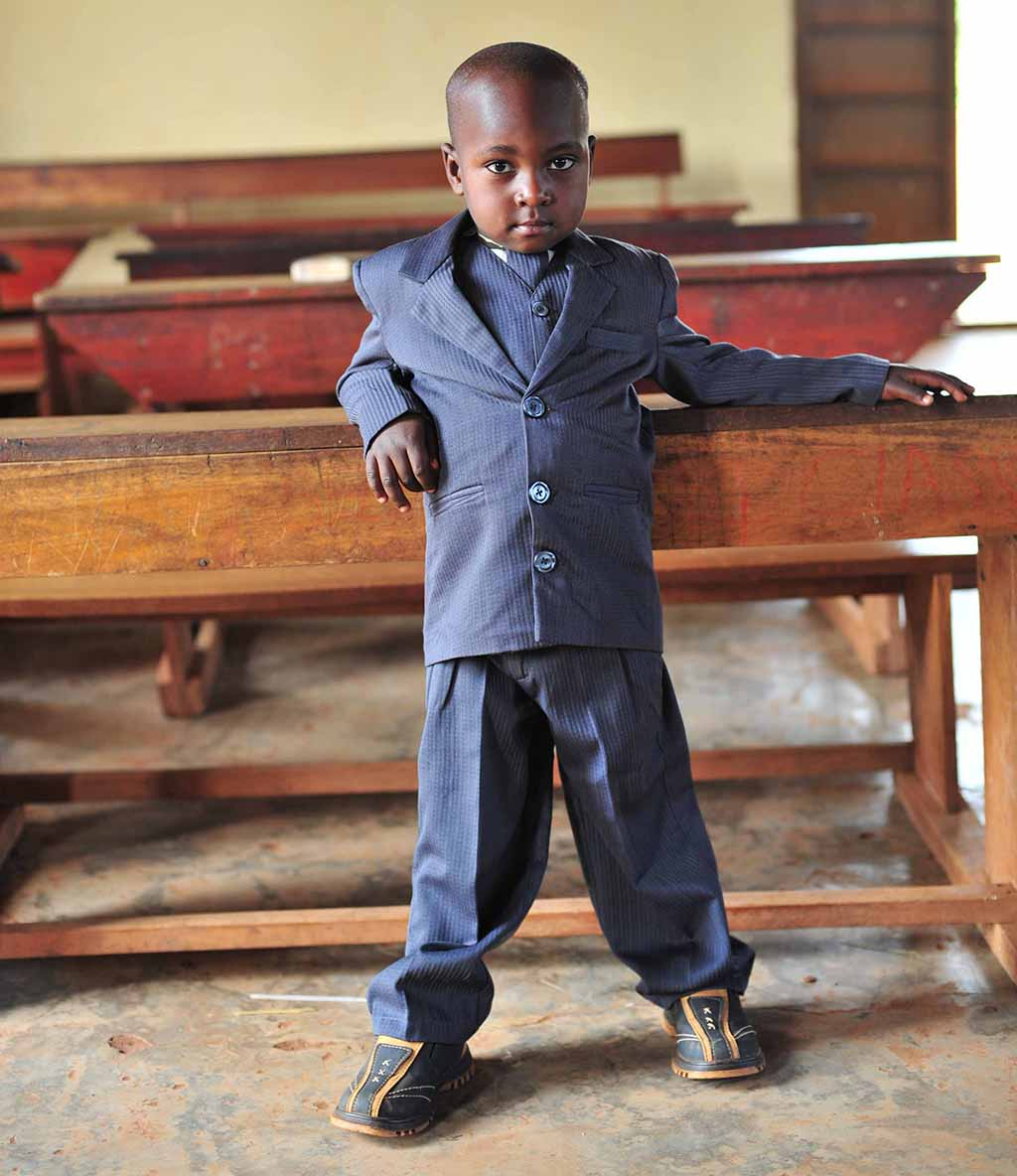 A small boy in a dark blue suit is standing in the classroom and leaning on the desk.