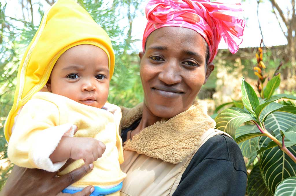 A mother is holding her small baby son in her arms as she stands outside in the yard. The baby has a yellow hood over his head and the mother hs a red scarf on her head.
