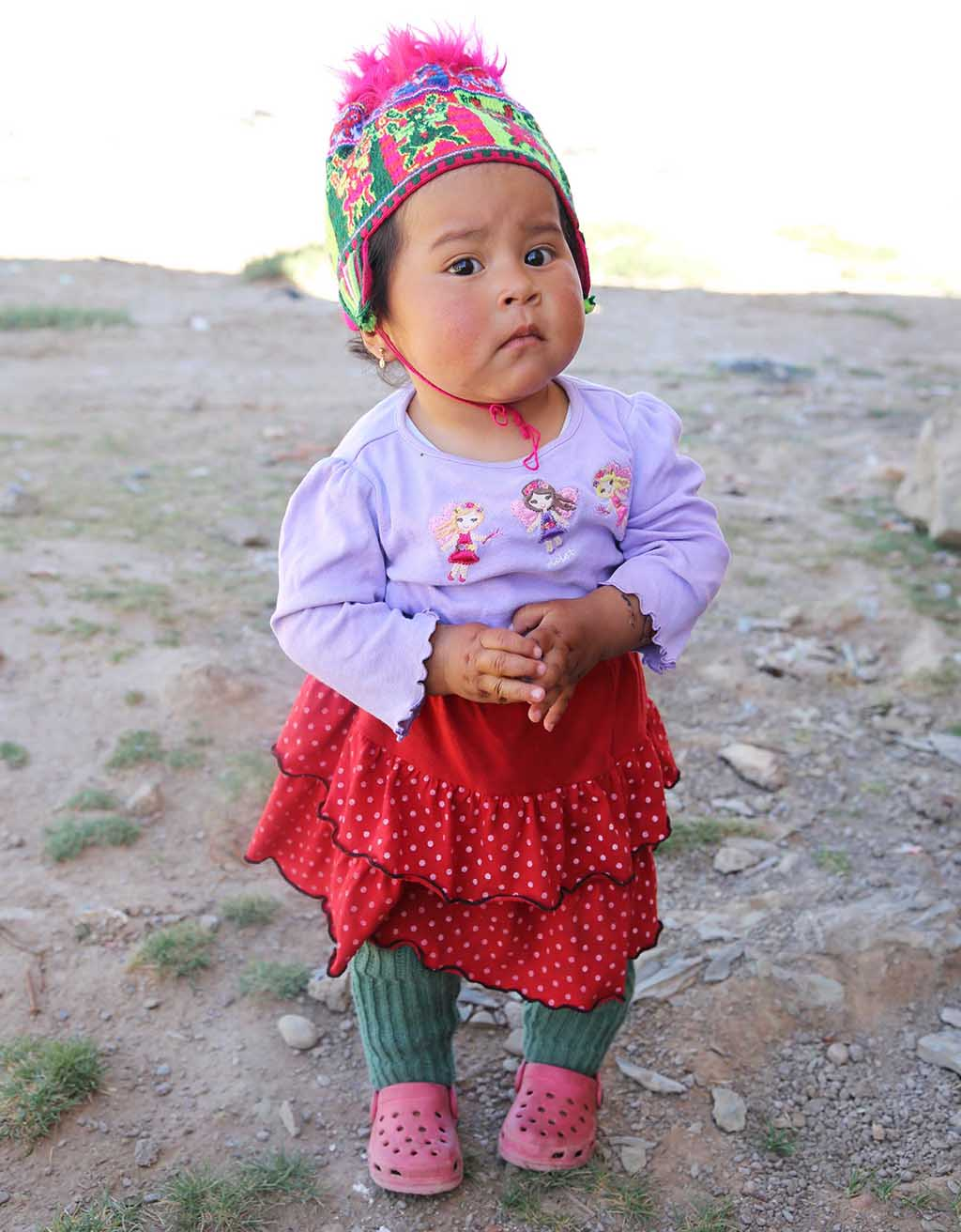 "A little girl in a purple shirt and red skirt is wearing a colorful hat and standing outside with her hands held in front of her. Children from the community are neglecter, however, ""Children will be raised with values, they will think in worshiping God, not in other things that aren't good for them. Mothers also will come and worship"" is the Pastor's hope and prayer."