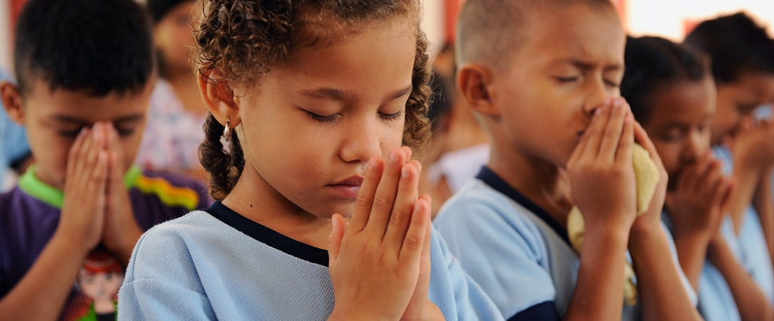 Close up of a project little girl, child, with hands folded, palms held together in prayer in front of her face and eyes closed as she prays. She is praying with other classmates, students, boys and girls, children, inside the project student center classroom.