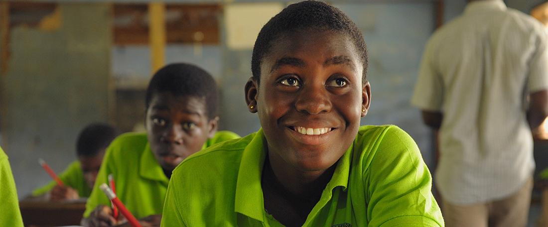 Ghanan students in classroom, wearing bright green uniforms and sitting at wood desks.