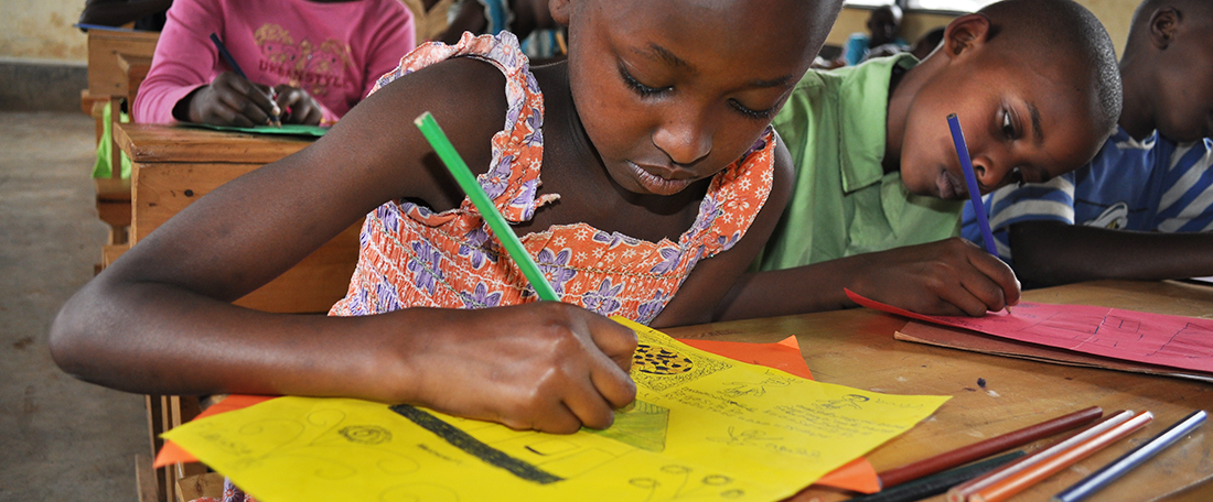 A child, girls, in close-up sits at her desk inside her classroom surrounded by other students, boys and girls, as she looks down drawing, coloring a picture on yellow paper for her sponsor, correspondence. She has a green pencil, coloring pencil in her hand.