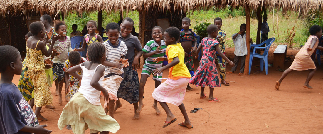 A group of project little young children, boys and girls, dancing, jump and play, participating in fun physical dancing activities, in a group together waving their hands in the hair and smiling happily.