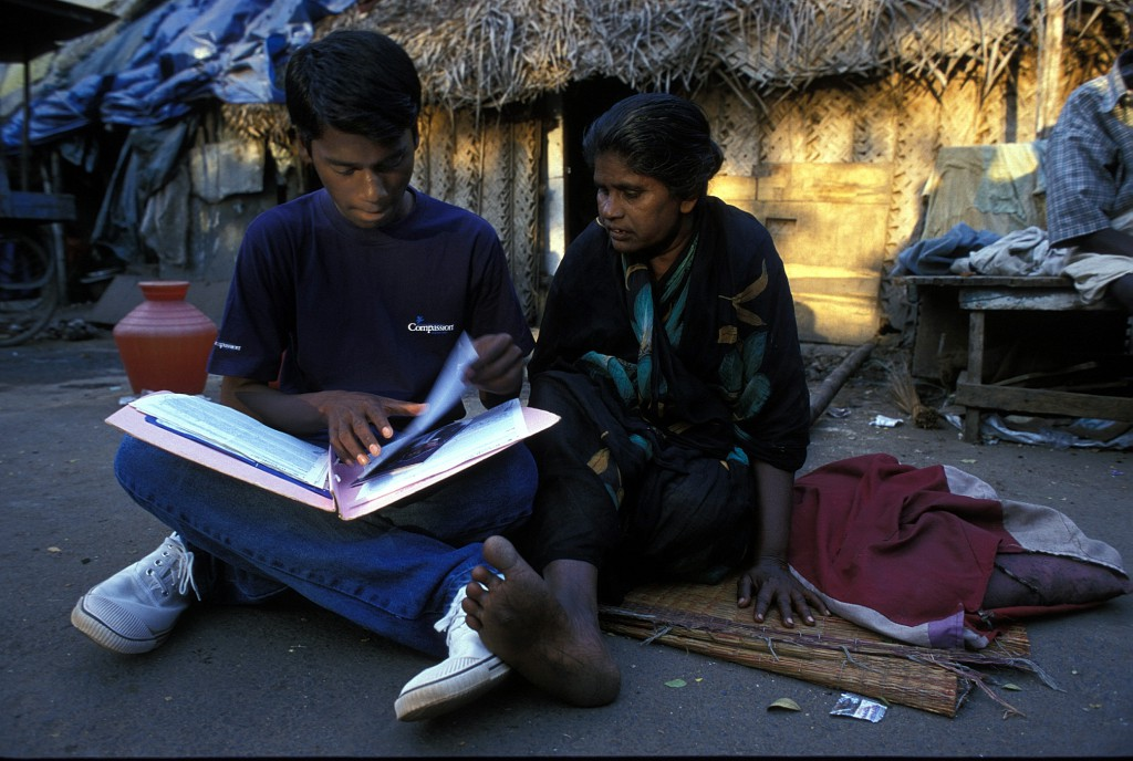 15-year-old Ramesh showing his prized book of letters and cards to his mother
