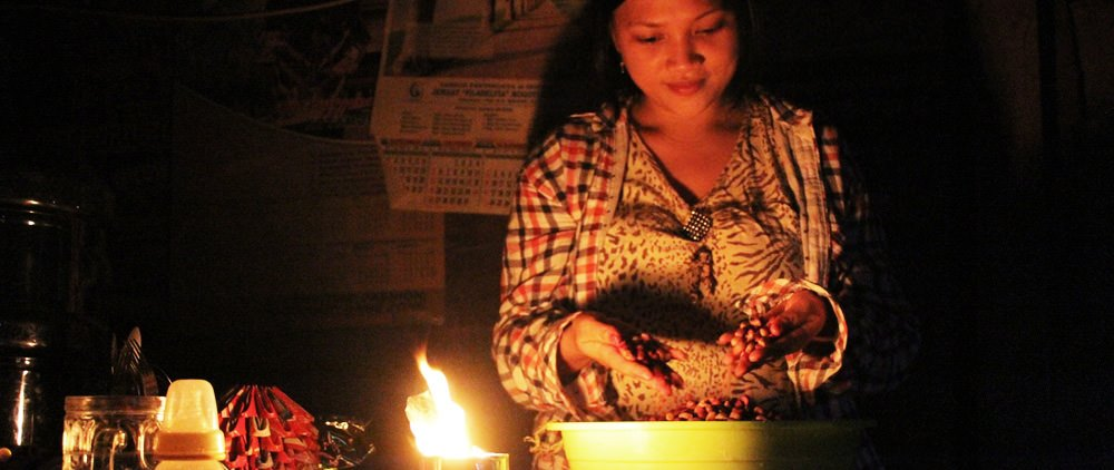 Sandy, a beneficiary of her local Compassion project in Indonesia, sorts beans in her kitchen by hand-made candle light. The hand-made candle was made from an empty metal food can during a workshop at the project.