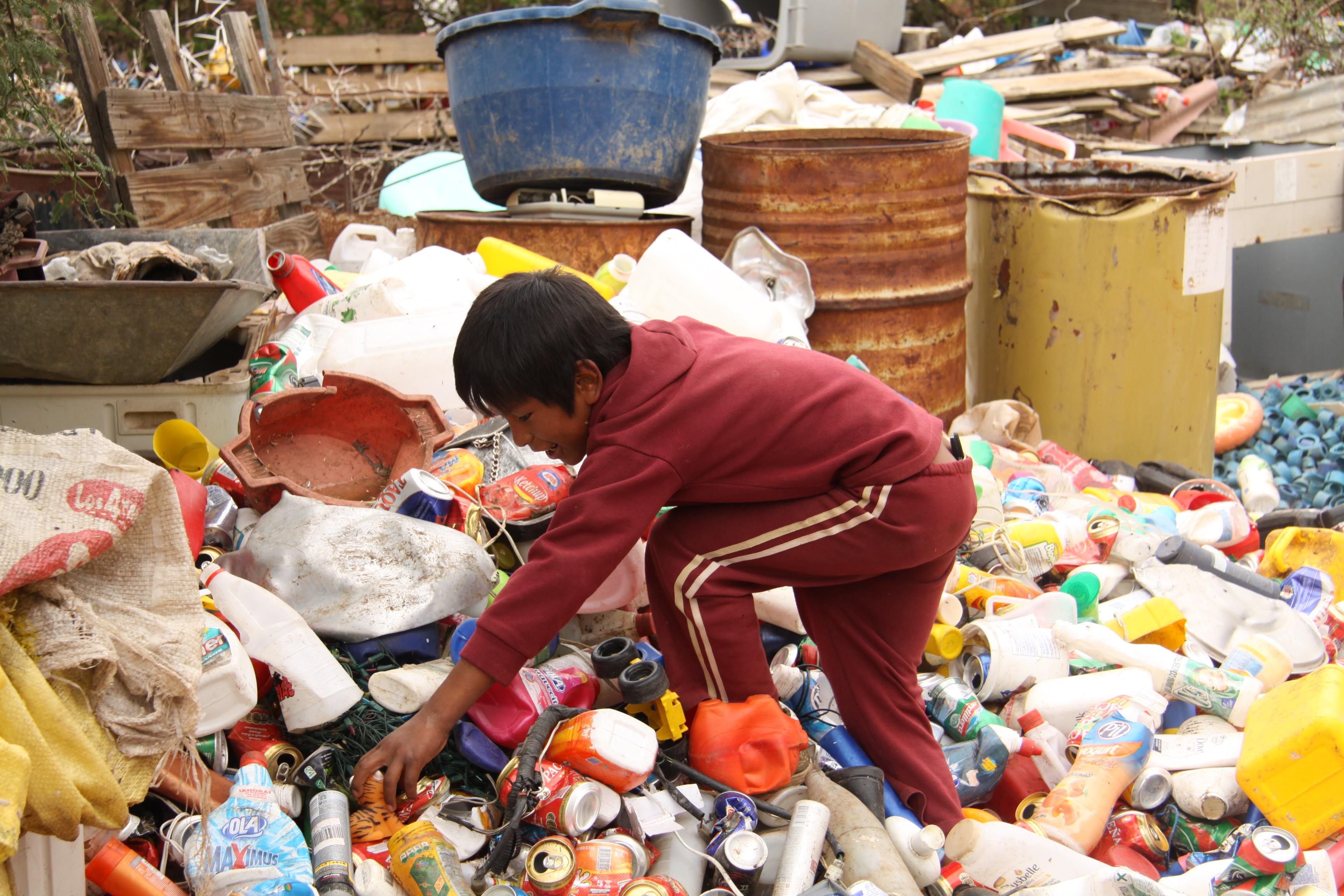 Bolivian sponsored child searches through rubbish