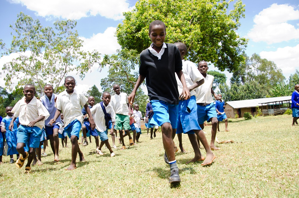 Juliius Otieno Oyalo runs with his friends happily outside in the green grass