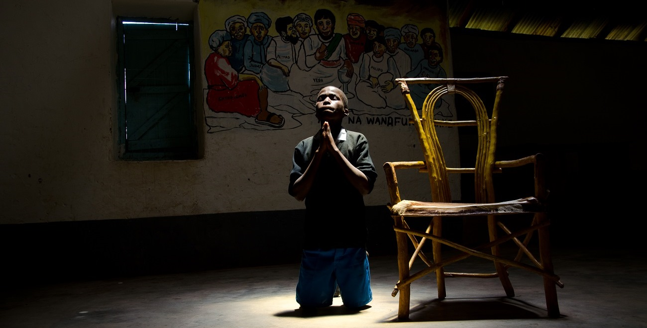 Julius praying at his Compassion project