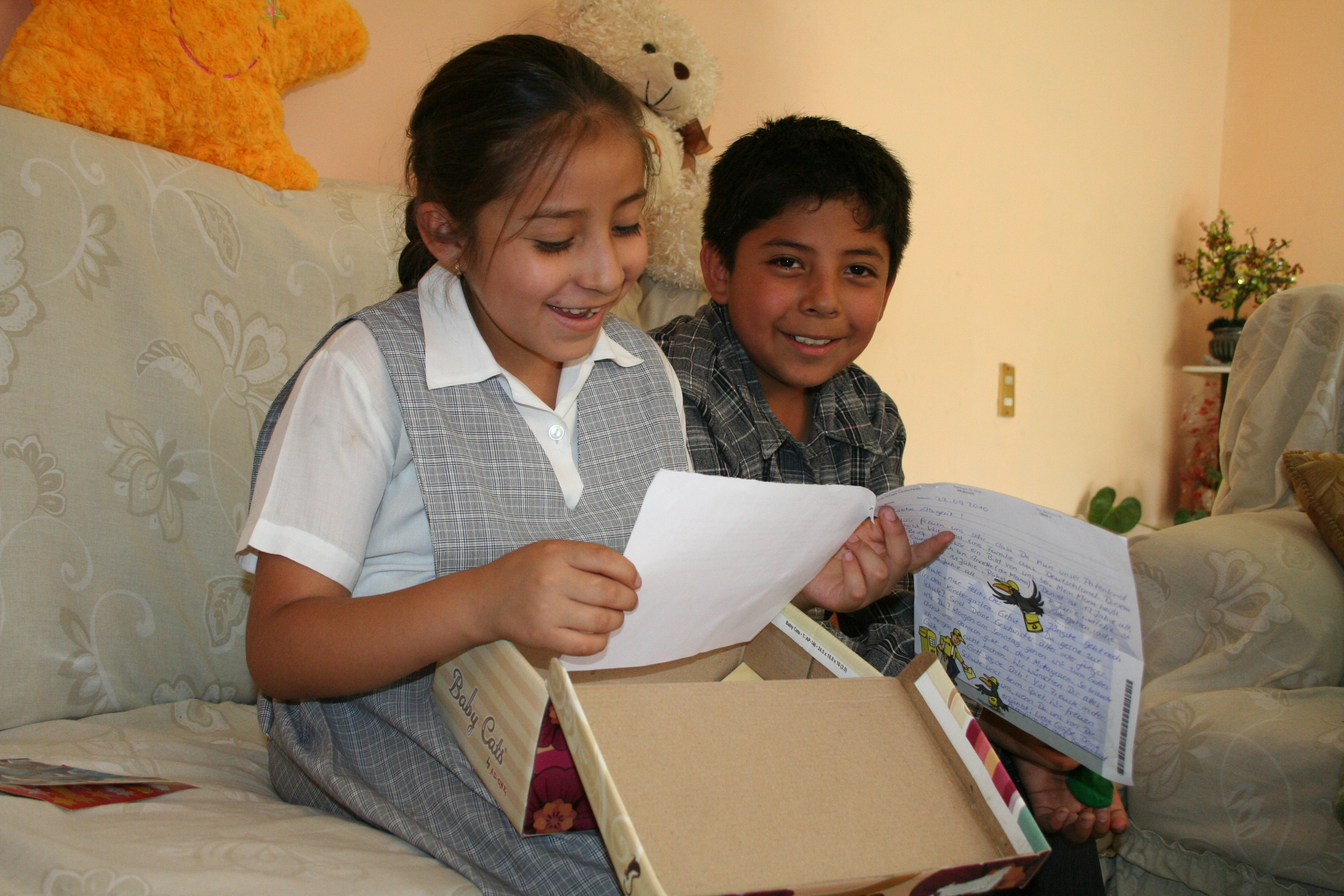 Belinda smiles looking down at a letter with her brother
