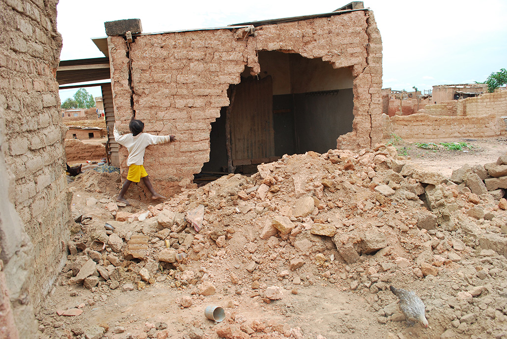 A child walks through rubble left behind after flooding at her house.  The brick house has a gigantic hole in the side of it.