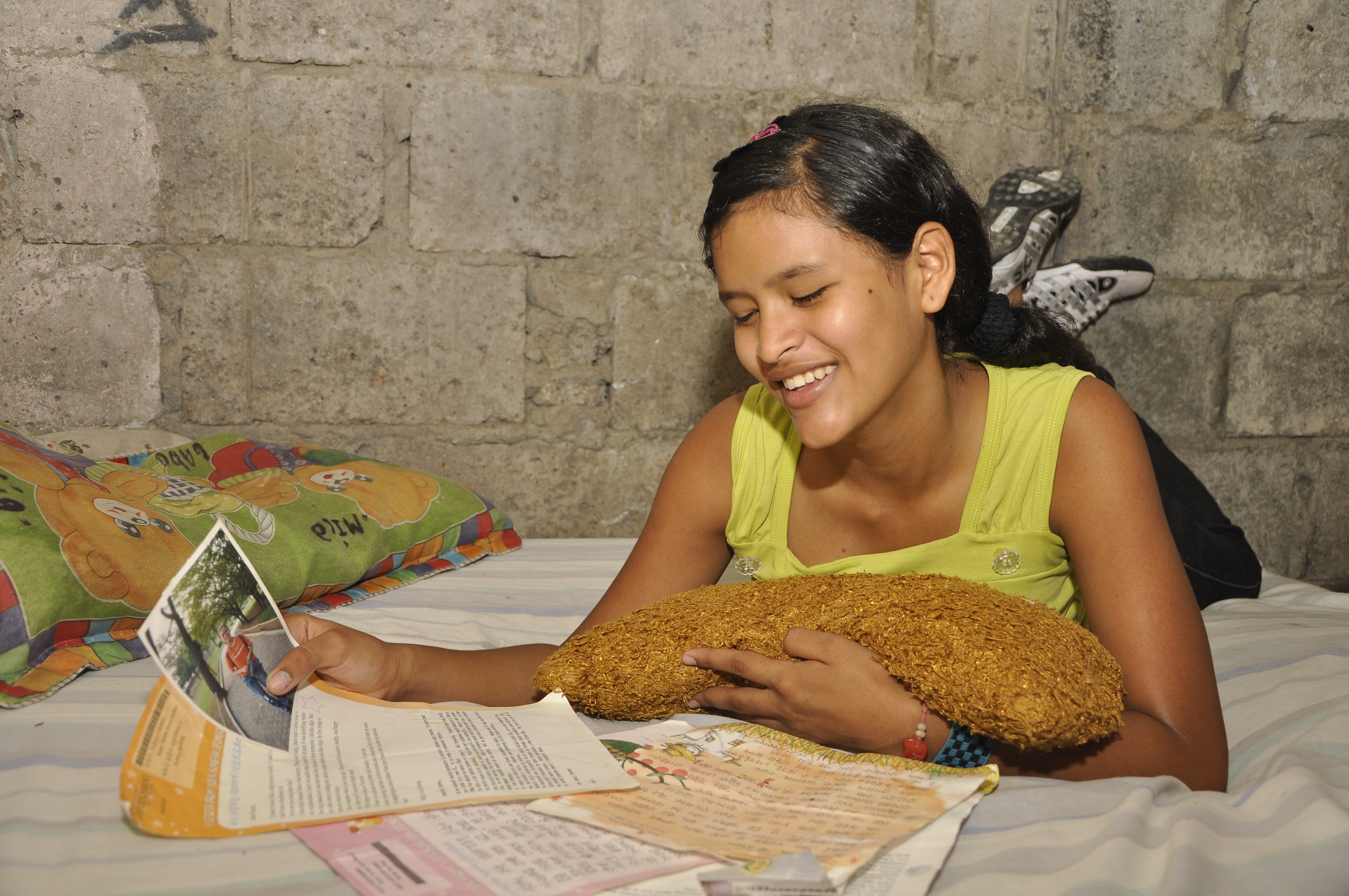Karen smiles reading sponsor letters and holding picture