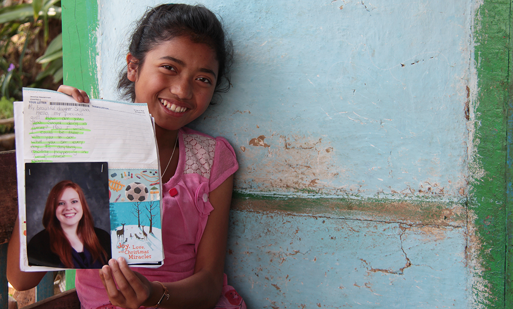 Young girl smiling holding up the letter from her sponsor