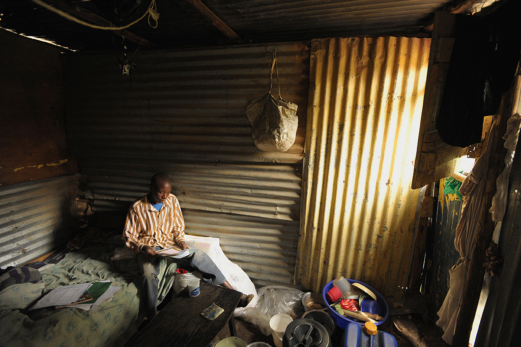 Kenyan child reading a letter from their sponsor in a tin room