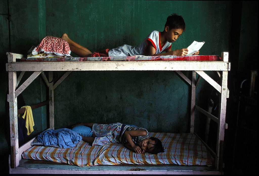 Abner on top bunk reading sponsor letter with younger brother on bottom of bunk in his home in Escopa area in Southeastern Quezon City.