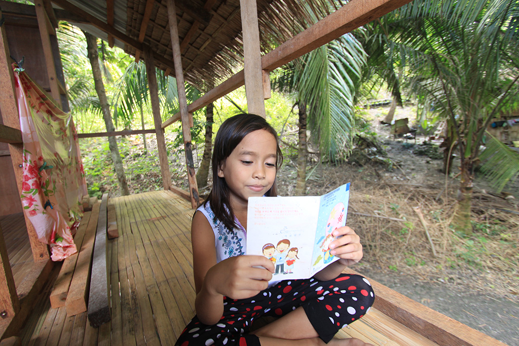 Merry Grace Legarde, a 8 year old child, girl smiles reading a sponsor letter, mail, correspondence letter, colorful cartoons, art, illustration on the front, on the small narrow wooden porch, balcony just outside her home with tropical green trees in the background.