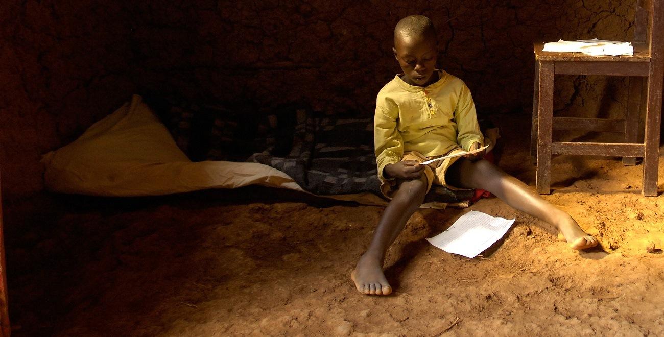 Rwandan boy reading letters