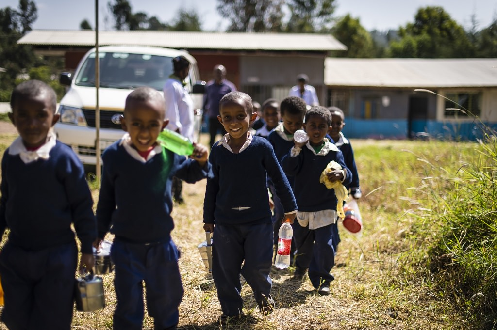 Sponsored children walking to the woodwork shed