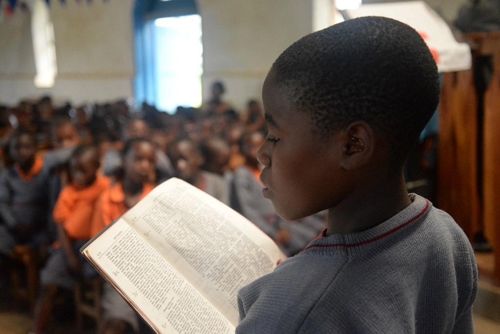 Sponsored child reading the Bible.