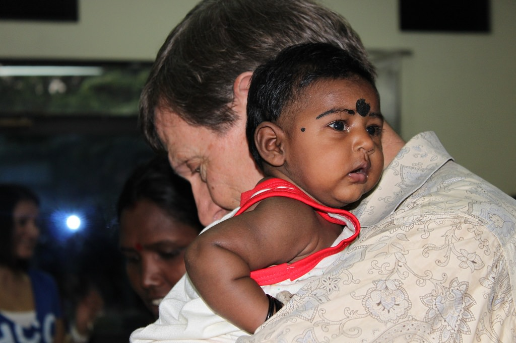 Wess Stafford cradling baby