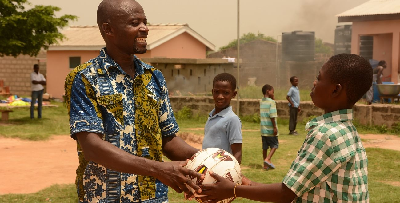 Compassion project worker Henry hands ball to a child