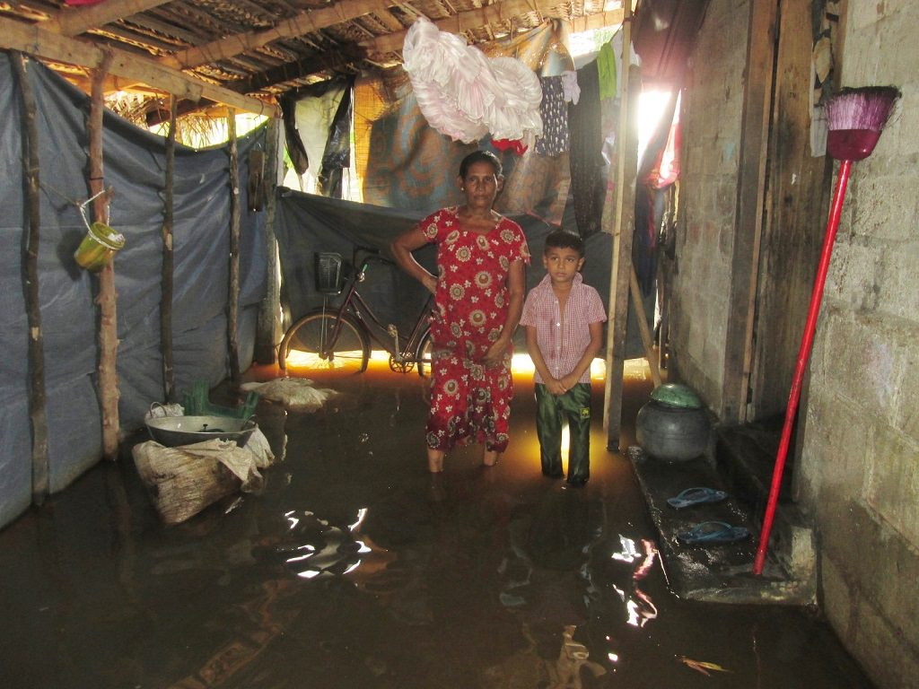 Sri Lankan mother and home in flooded home