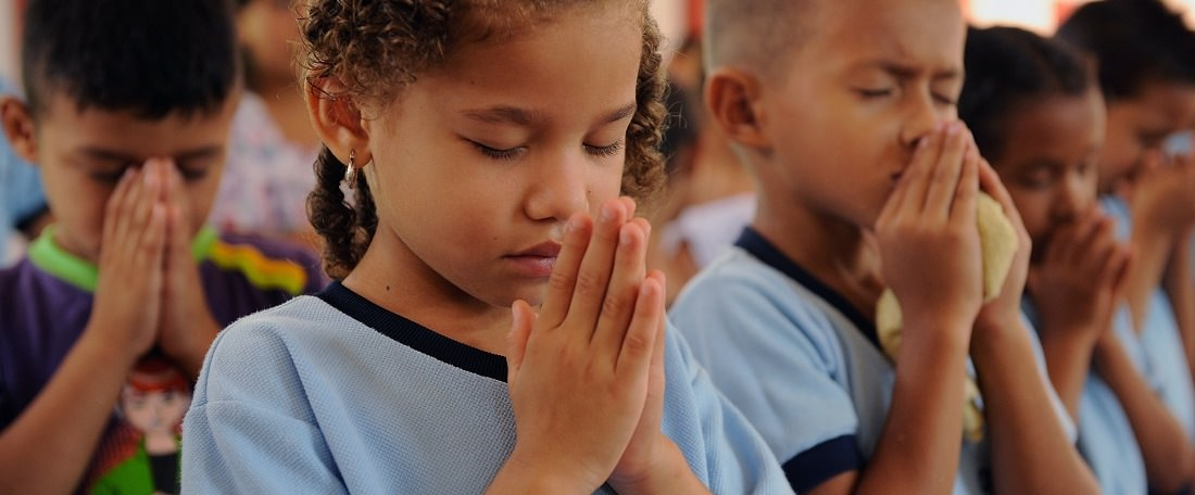 Children praying in Colombia