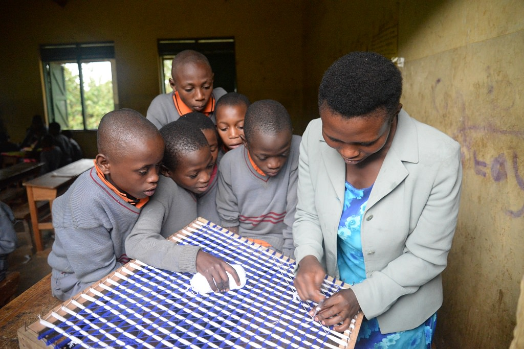 Learning weaving at a Compassion project in Uganda