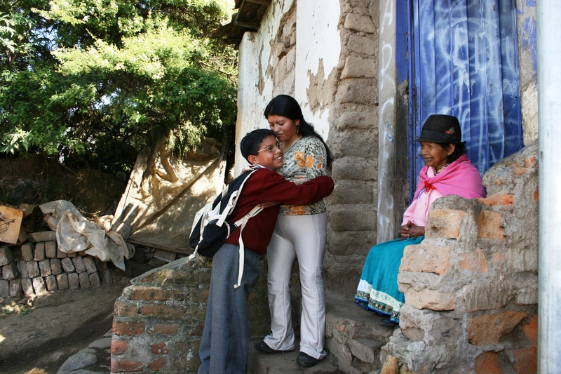Bolivian sponsored child hugs his mother