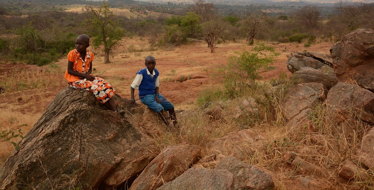 Kenyan siblings sit on rock