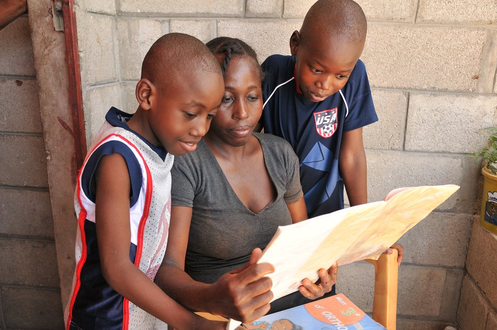 Haitian boys showing their mum their homework