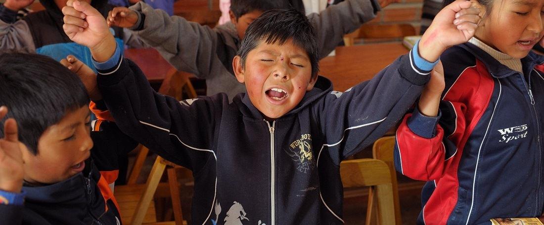 Bolivian boy worshipping God