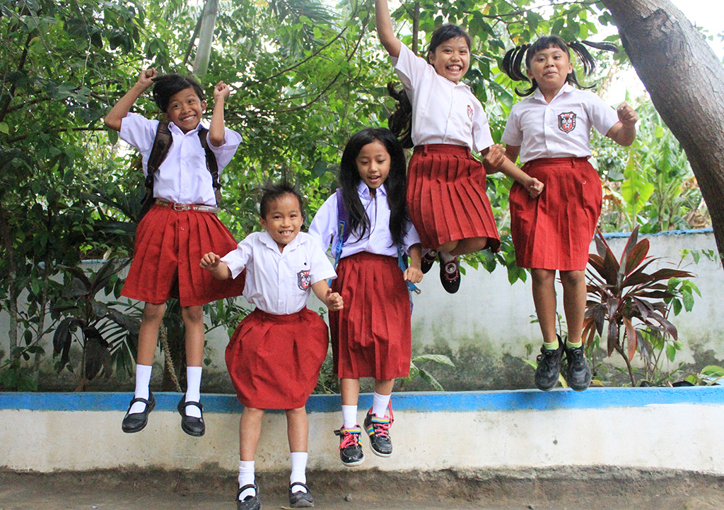 Bintang and her friends jump together for a photo