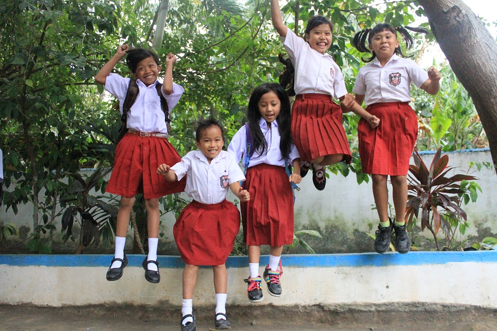 Girls jumping in Indonesia outside Compassion project