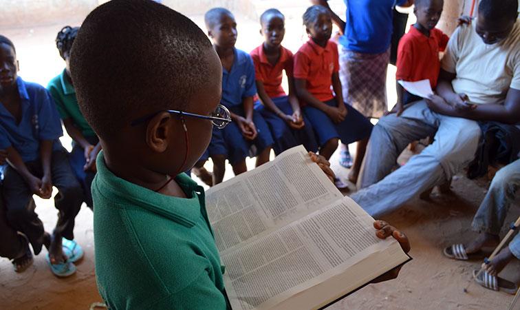 Boy reading Bible in Tanzania