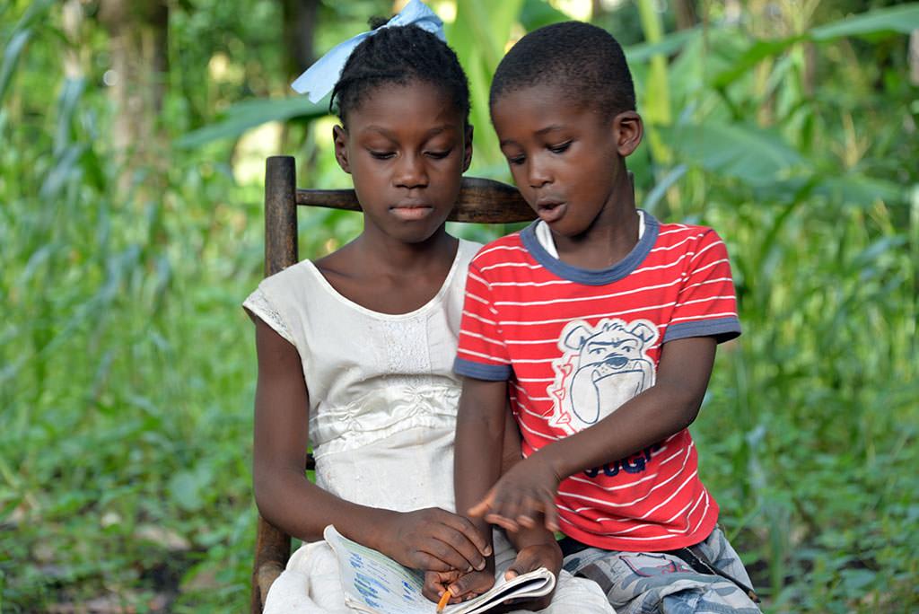 Haitian sponsored child Nadiane teaches her cousin