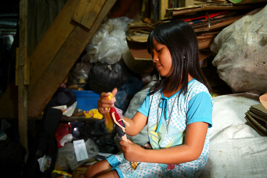 Girl playing with a Barbie in Indonesia