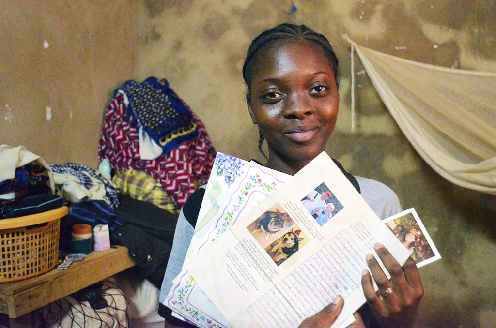 Alcha from Burkina Faso holding letters from her sponsor