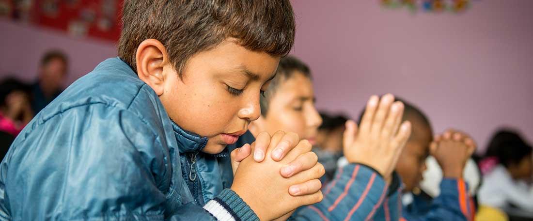 Boys praying in Ecuador