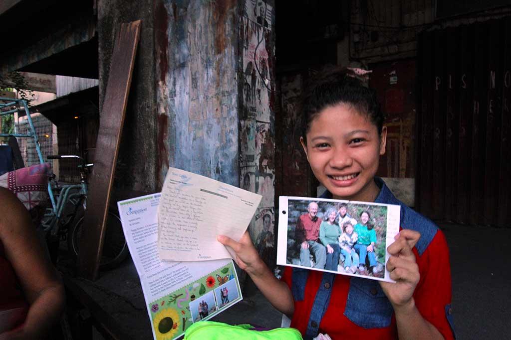 Sponsored child Jennylin holding letters from her sponsor