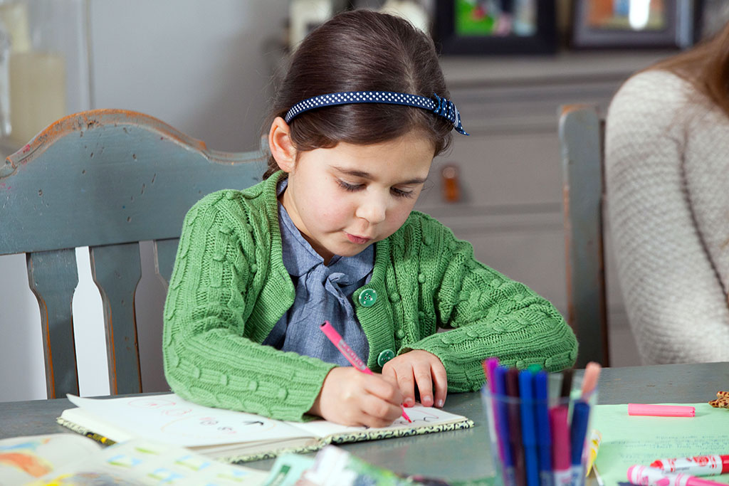 Child writing a letter to her sponsored child