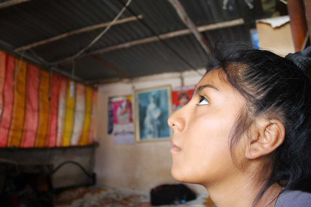 Sponsored child Jenifer looking up at her roof