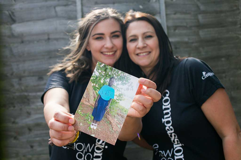 Compassion sponsors Tania and Caitlin hold up photo of sponsored child