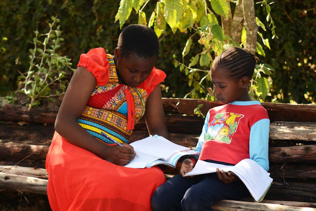 Sponsored child Ruth teaching her sister