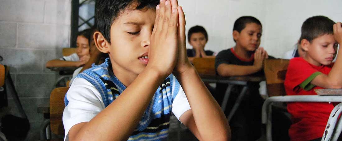 Boy praying in El Salvador