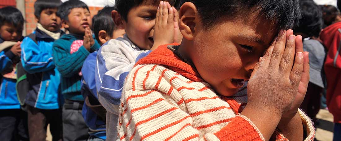 Boys praying in Bolivia