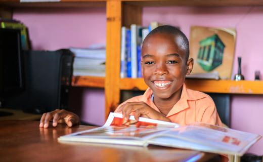 Wendyj, a boy from Haiti, reads a magazine